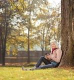Mädchen, das durch einen Baum im Park sitzt und sms schreibt Lizenzfreies Stockfoto