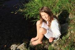 Mädchen, das durch einen Fluss sitzt Stockbilder