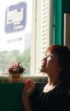 Mädchen, das durch Fenster schaut lizenzfreie stockfotografie