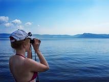 Mädchen, das durch Ferngläser auf einer Horizontlinie schaut lizenzfreie stockfotografie