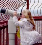Mädchen, das durch Ferngläser schaut Stockfotografie
