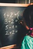 Mädchen, das durch Finger berechnet, um die Antwort auf Tafel zu schreiben stockbild