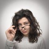 Mädchen, das durch Gläser schaut Stockfotografie