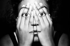 Mädchen, das durch ihre Hände schaut stockfotografie