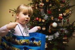Mädchen, das durch Weihnachtsbaum spielt Stockbild
