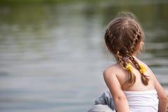 Mädchen, das durchdacht auf dem Fluss schaut Lizenzfreie Stockfotos