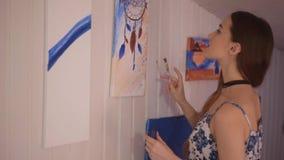 Mädchen, das ein Bild im Hauptstudio malt Vorbildliche Frau, die ihr Bild malt Kunst Frau zeichnet Farben Dreamcatcher stock footage