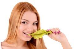Mädchen, das ein Blatt des Kopfsalates beißt Stockfoto
