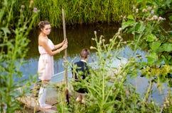 Mädchen, das in ein Boot schwimmt Lizenzfreies Stockfoto