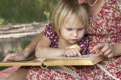 Mädchen, das ein Buch auf dem Schoss seiner Mutter liest Lizenzfreies Stockfoto