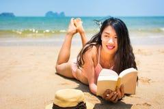 Mädchen, das ein Buch auf dem Strand liest lizenzfreie stockfotos