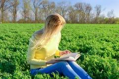 Mädchen, das ein Buch auf einem Gebiet liest Stockbilder