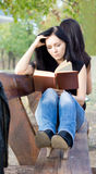 Mädchen, das ein Buch auf einer Bank liest Lizenzfreies Stockbild