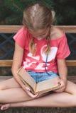 Mädchen, das ein Buch auf einer Bank liest Stockfoto
