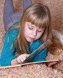 Mädchen, das ein Buch beim Lügen auf Teppich liest lizenzfreies stockbild