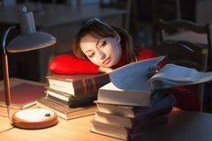 Mädchen, das ein Buch in der Bibliothek unter der Lampe liest lizenzfreie stockfotografie