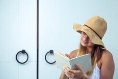 Mädchen, das ein Buch an der Tür liest stockfotos