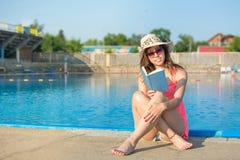 Mädchen, das ein Buch durch das Pool liest Lizenzfreie Stockfotos