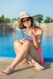 Mädchen, das ein Buch durch das Pool liest Stockfotos