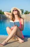 Mädchen, das ein Buch durch das Pool liest Stockbild
