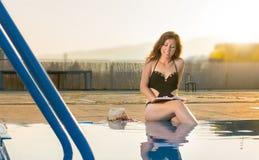 Mädchen, das ein Buch durch das Pool liest lizenzfreie stockbilder