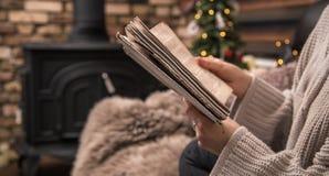 Mädchen, das ein Buch in einer gemütlichen Hauptatmosphäre nahe dem Kamin, Nahaufnahme liest lizenzfreie stockfotos