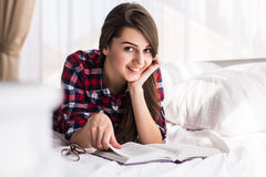 Mädchen, das ein Buch im Bett, liegend auf ihrem Magenlächeln glücklich und entspannt an einem Freizeittag liest Stockbild
