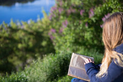 Mädchen, das ein Buch im Park auf der Bank liest Lizenzfreies Stockfoto