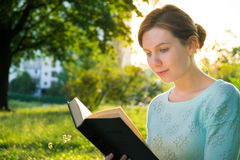 Mädchen, das ein Buch im Park liest Stockfotos