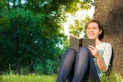 Mädchen, das ein Buch im Park liest Lizenzfreie Stockbilder