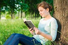 Mädchen, das ein Buch im Park liest Lizenzfreies Stockfoto