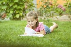 Mädchen, das ein Buch im Park liest stockfoto