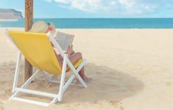 Mädchen, das ein Buch im Sonnenstuhl am Strand liest Lizenzfreie Stockfotografie