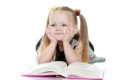 Mädchen, das ein Buch liegt auf dem Boden liest Stockfotografie