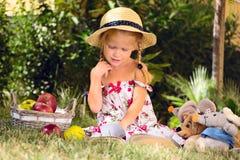 Mädchen, das ein Buch mit den Spielwaren im Garten liest Stockfotografie