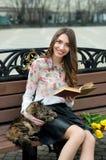 Mädchen, das ein Buch mit einer Katze auf einer Bank in der Stadt liest Stockbild