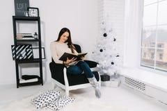 Mädchen, das ein Buch nahe Weihnachtsbaum liest lizenzfreies stockfoto