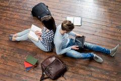 Mädchen, das ein Buch und einen Jungen verwendet eine Tablette liest Lizenzfreie Stockfotos