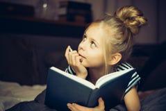 Mädchen, das ein Buch und Träume im Bett liest lizenzfreie stockbilder