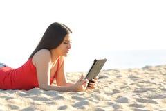 Mädchen, das ein ebook oder eine Tablette auf dem Strand liest Stockbild