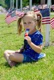 Mädchen, das ein Eis am Stiel auf Juli 4. genießt Stockbilder