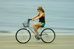 Mädchen, das ein Fahrrad auf den Strand reitet Stockfotos