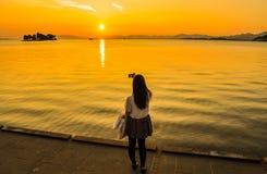 Mädchen, das ein Foto des Sonnenuntergangs über einem See macht lizenzfreie stockbilder