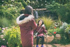Mädchen, das ein Foto ihrer Schwester im Freien im Park mit Mobiltelefon macht Lizenzfreie Stockfotos