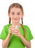 Mädchen, das ein Glas Milch hält Stockfotos