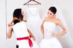 Mädchen, das ein Hochzeitskleid wählt Stockfotografie