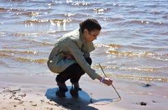 Mädchen, das ein Inneres auf dem Sand malt Stockfoto