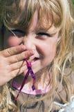 Mädchen, das ein Lächeln versteckt Lizenzfreie Stockfotografie