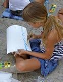 Mädchen, das ein Meer auf Asphalt zeichnet Stockfotos
