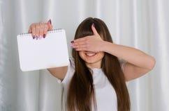 Mädchen, das ein Notizbuch anhält Lizenzfreie Stockfotos
